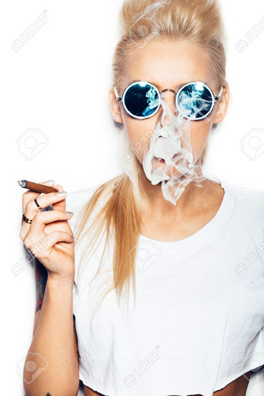 Banque d images - Femme blonde sexy en lunettes de soleil et t-shirt blanc  soufflant la fumée d un cigare. Swag fille de style avec lumineux  maquillage et ... b07c5bc9a1af