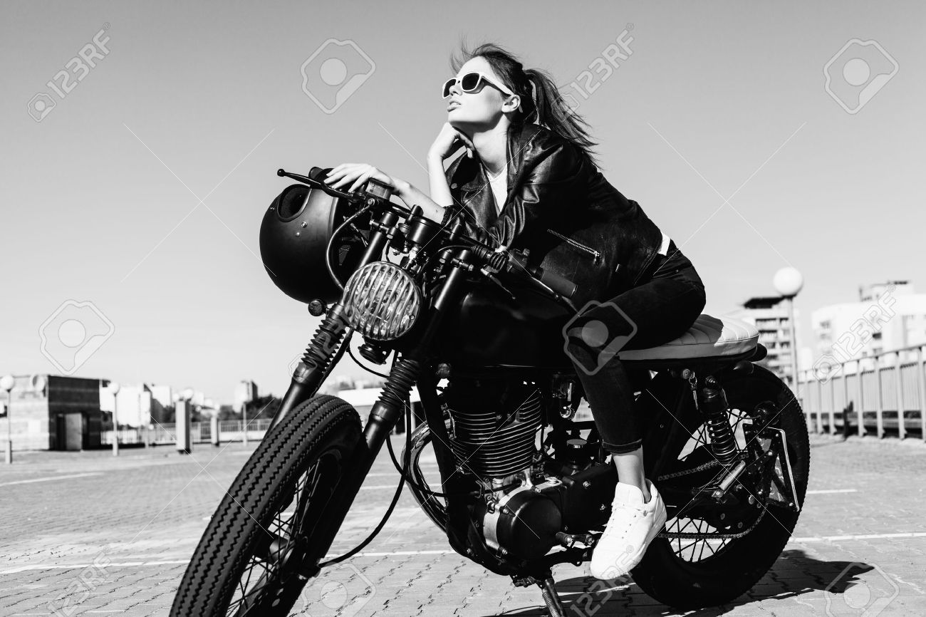 Biker girl sitting on vintage custom motorcycle black white outdoor lifestyle portrait stock photo