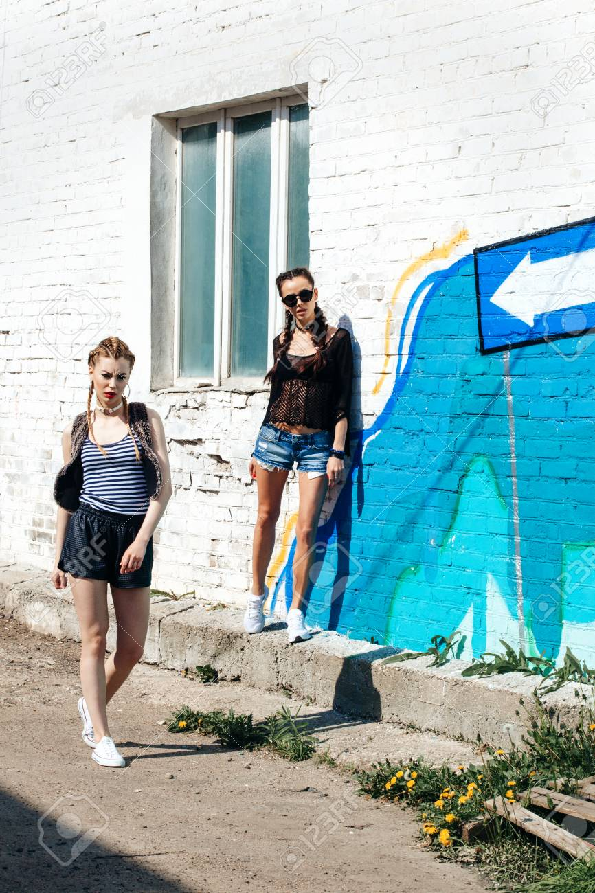 Bright Stylish Lifestyle Outdoor Portrait Of Two Pretty Best Friends Girls Posing At Street Urban