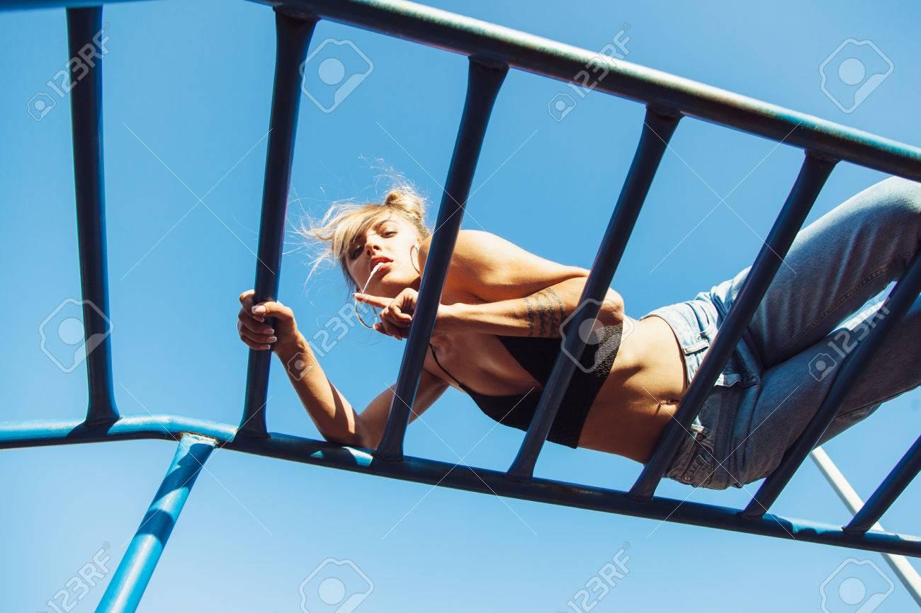 6301569d7614f Aktive junge Frau auf Leiter ausüben. Sportlich fit Mädchen bei  Outdoor-Fitness-Studio