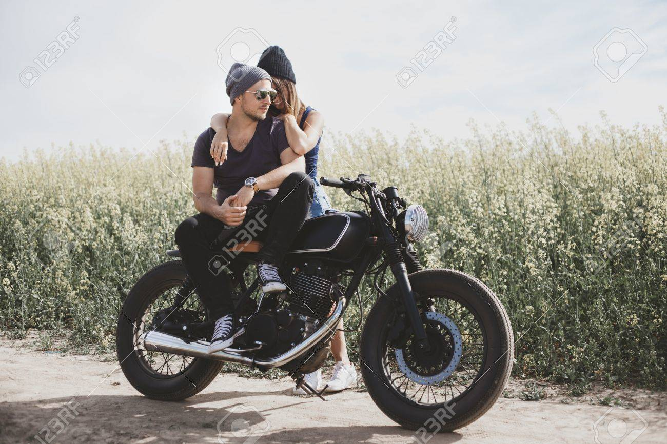 couple motorcycle love photo  Young Romantic Couple In A Field On A Motorcycle. Love, Freedom ...
