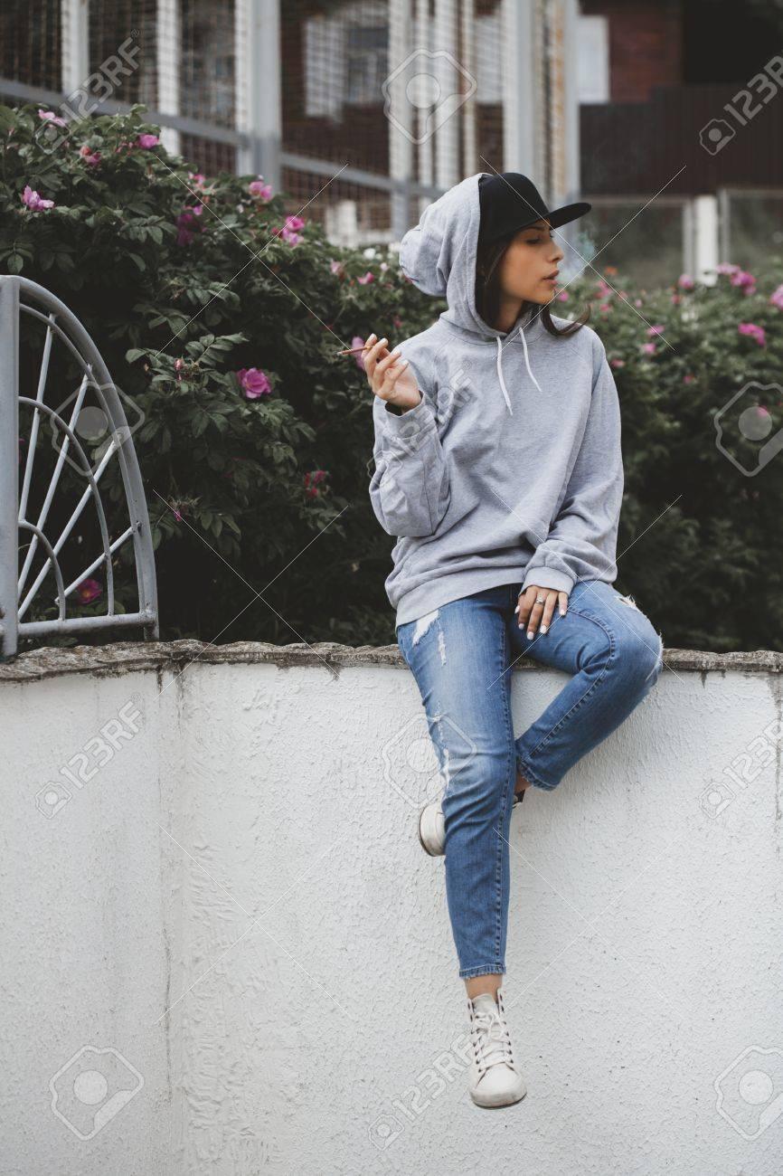 Portrait de style de vie extérieur jeune femme assise sur le sol sur la  place, fumant une cigarette. Hoodie, cap, jeans, snickers swag girl concept