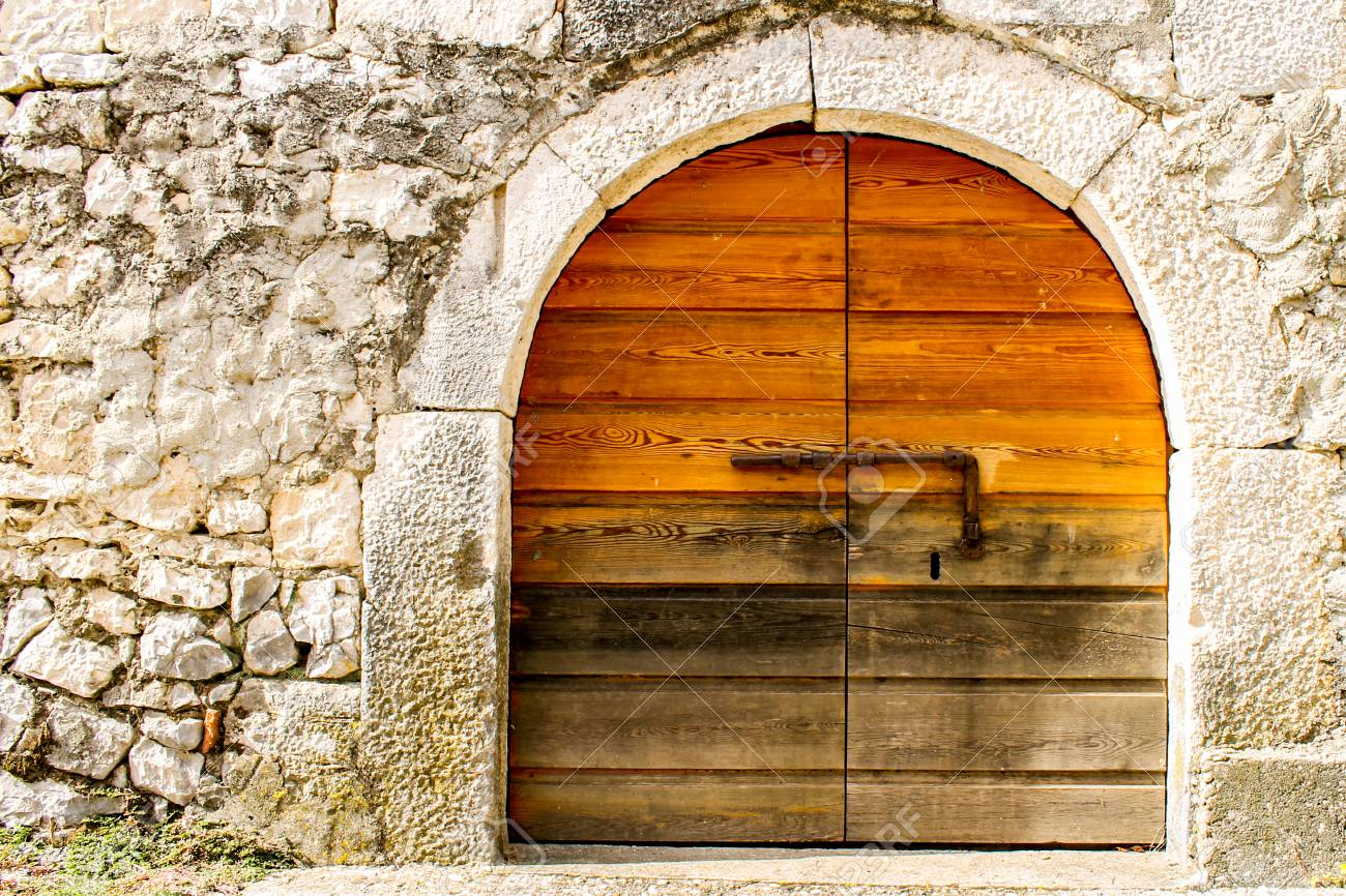 A Round Wooden Door On A Rock Wall Stock Photo   92114074