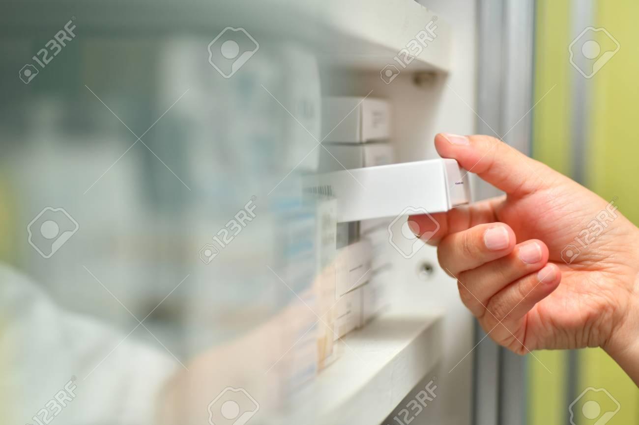 Pharmacist holding medicine box and capsule pack in pharmacy drugstore. - 100324770