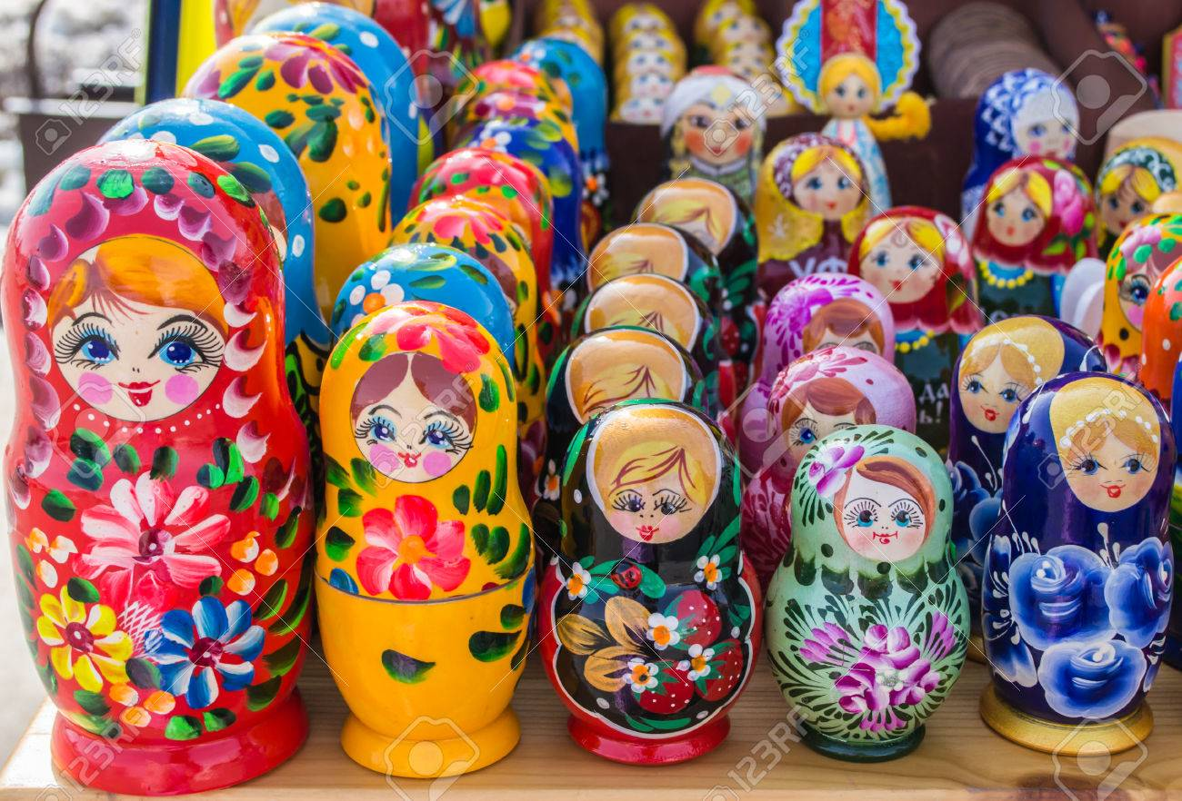 Rows of the Russian puzzle nesting dolls in various colours - 37874250