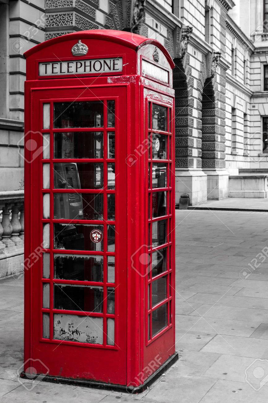Single red telephone booth in London in bright red paint and with  desaturated colors with no