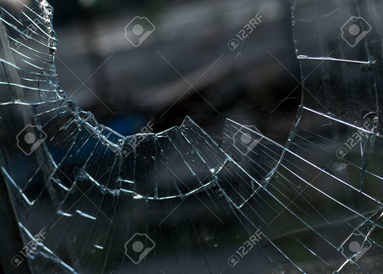 Closeup shot of a smashed broken glass window pane with a very blurred background and a disturbing viewing angle - 45132980