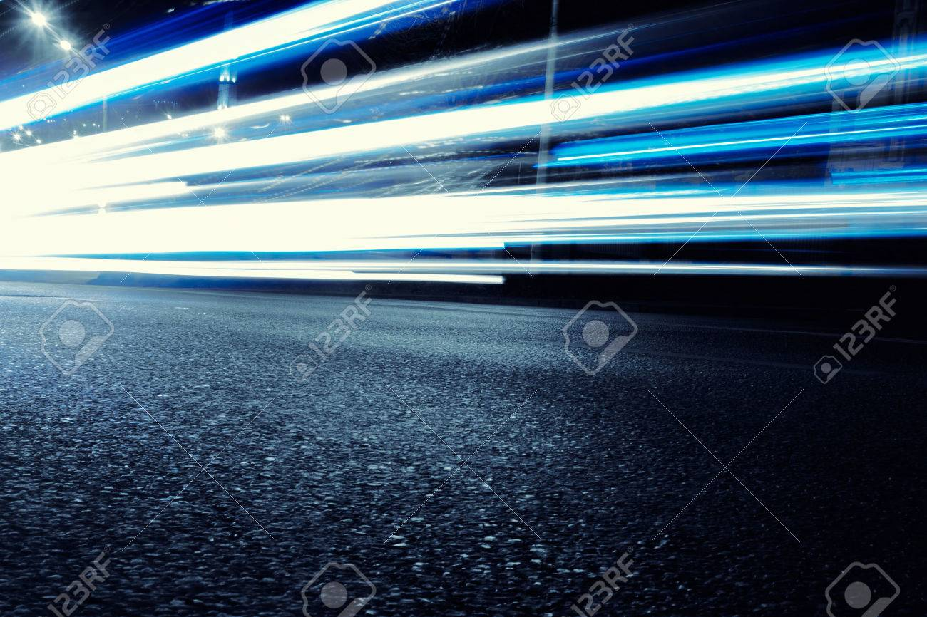 Cars Create Light Blue Light Trails From Their Headlights As They Move In A  City During