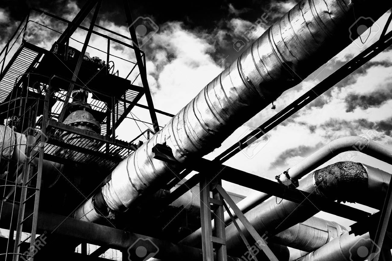 Metal industrial piping of a factory that carries water/gas/materials and metal walkways with a cloudy sky in black and white monochrome - 46797932