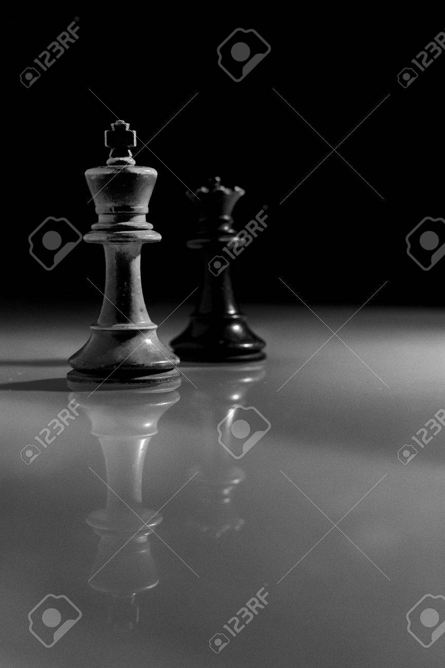 Single wooden white king and black queen chess pieces reflected from a glass surface monochrome