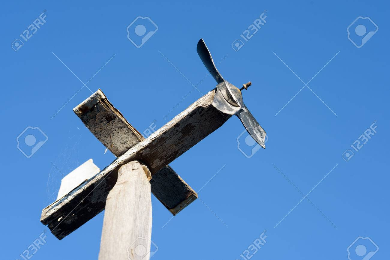 Homemade wooden airplane weather vane with a blue summer sky Stock Photo - 65460262
