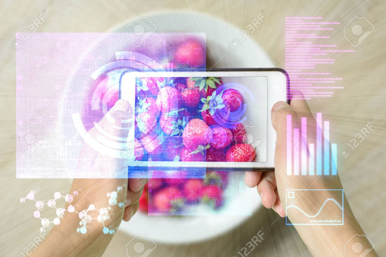 Woman holding a smart device uses reality augmentation to examine a pile of strawberries - 83355972