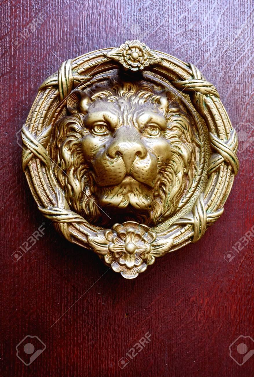 Single golden coloured brass lions head door knocker and vintage antique  wooden door in dark burgundy - Single Golden Coloured Brass Lions Head Door Knocker And Vintage