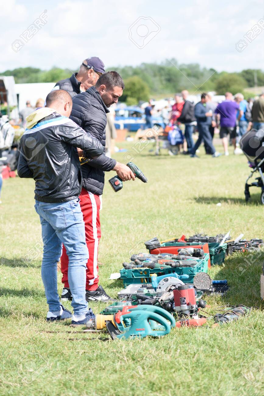 CHELMSFORD, ESSEX/ENGLAND - 1ST JUNE 2019 - Men visiting a car boot sale in Boreham Essex where they are looking at drills and tools for work and can also buy cheap and unusual items during the summer of 2019 - 143725280