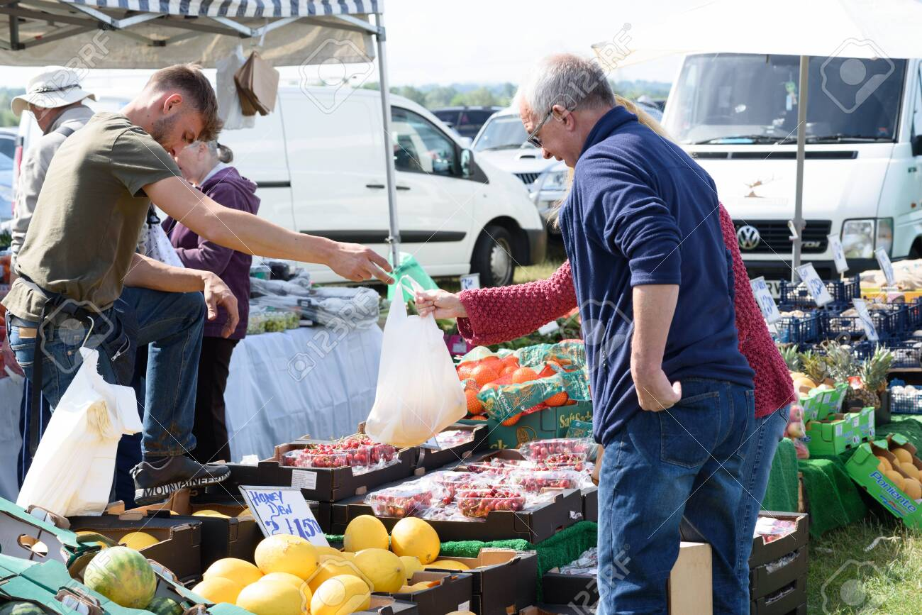 CHELMSFORD, ESSEX/ENGLAND - 1ST JUNE 2019 - People visiting a car boot sale in Boreham Essex buying fruit and vegetables and where they can also buy cheap and unusual items during the summer of 2019 - 143725283