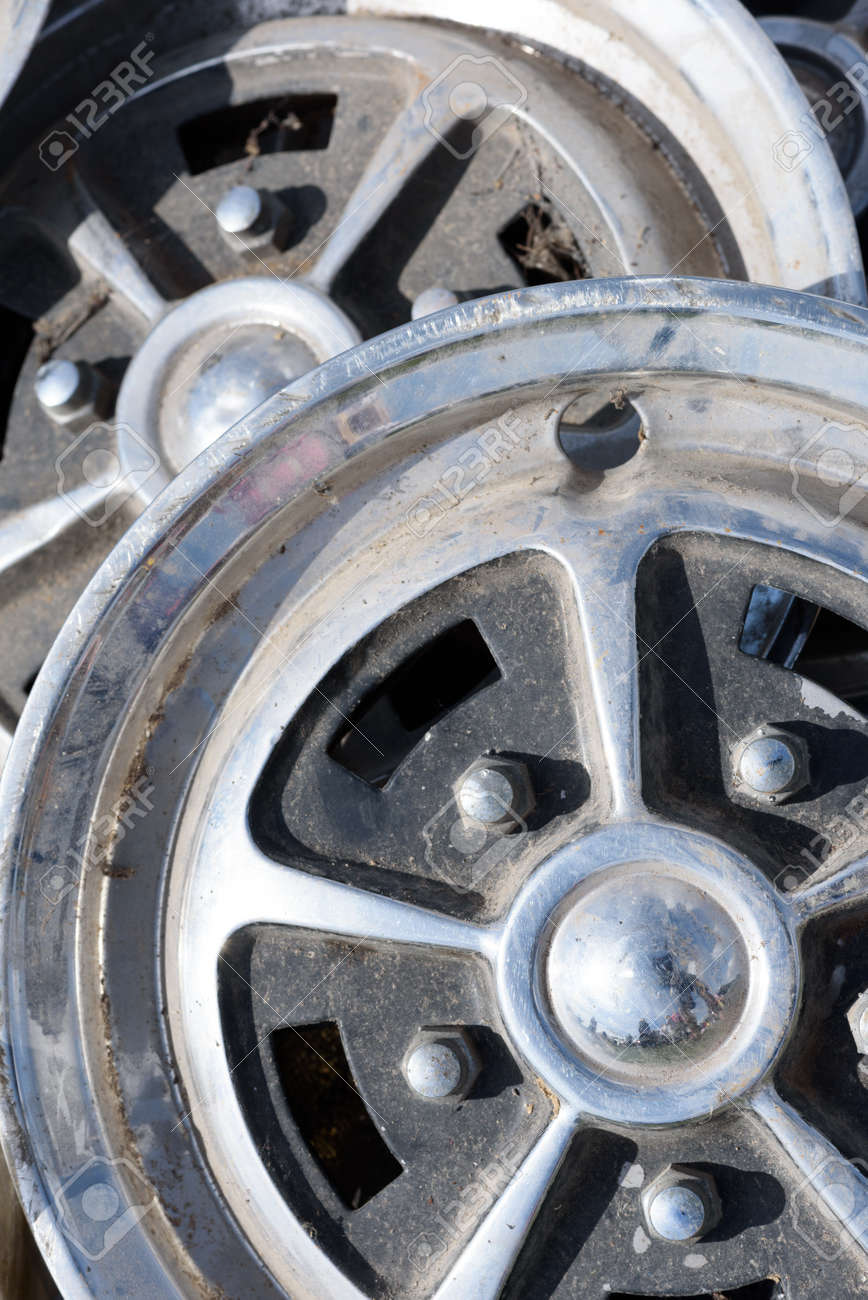 Closeup of tow car wheel trims in alloy metal silver with dirt and grime showing their used condition - 155300736