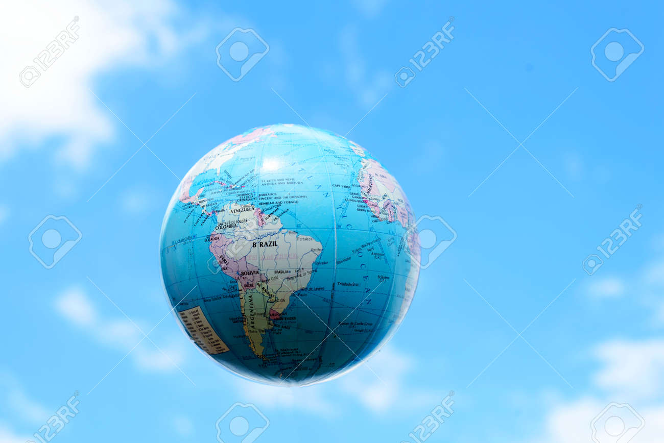 Artificial plastic globe of planet earth floating in a blue sky with clouds and copyspace area for planetary sci-fi ideas and concepts - 150672336