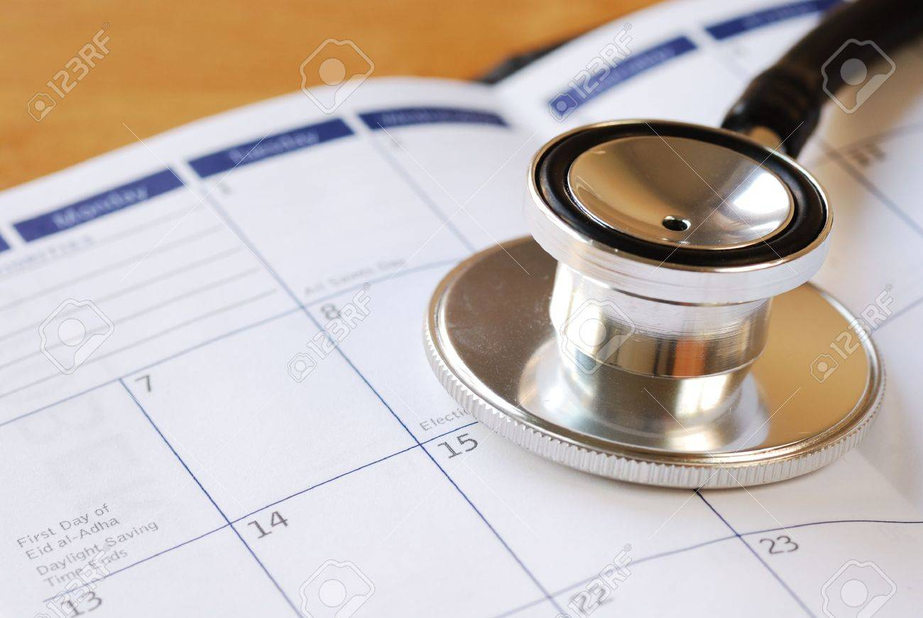 a stethoscope on the calendar concepts of medical appointment stock