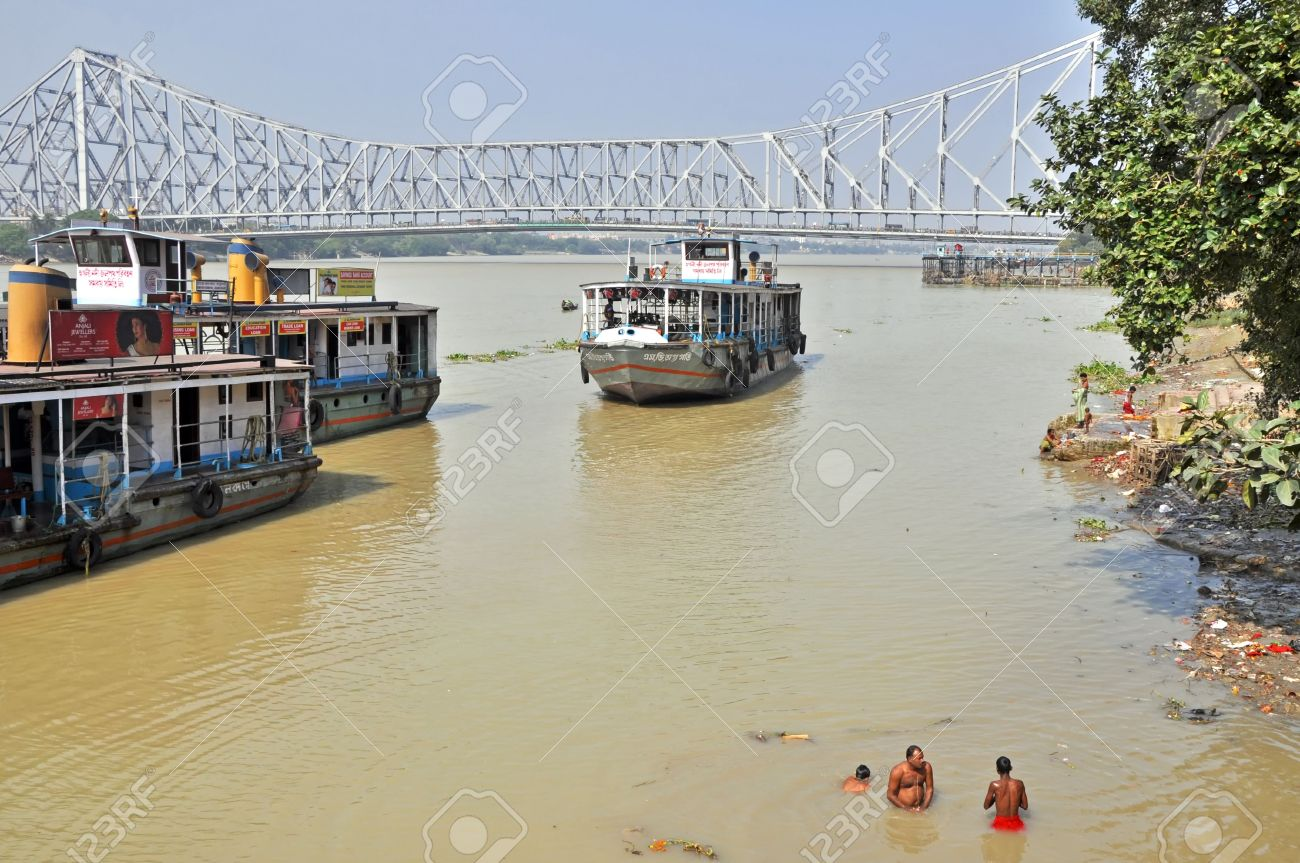 KOLKATA, INDIA - 27 OCTOBER 2009: An unidentified indian men wash themselves in Hooghly River on October 27, 2009. At present time this river, like the others in India, is being polluted tremendously. Stock Photo - 8151672