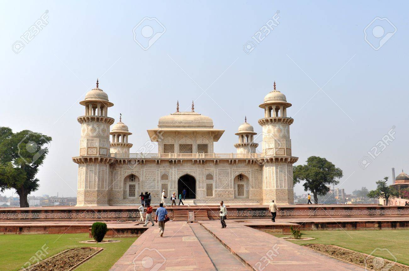 AGRA, INDIA - 2 NOVEMBER, 2009: Tourists walk in the front of the finest example of Mughal architecture - Itmad-ud-Daulas Tomb, on November 2, 2009. Sometimes called the Baby Taj, the tomb is often regarded as a draft of the Taj Mahal. Stock Photo - 8449044
