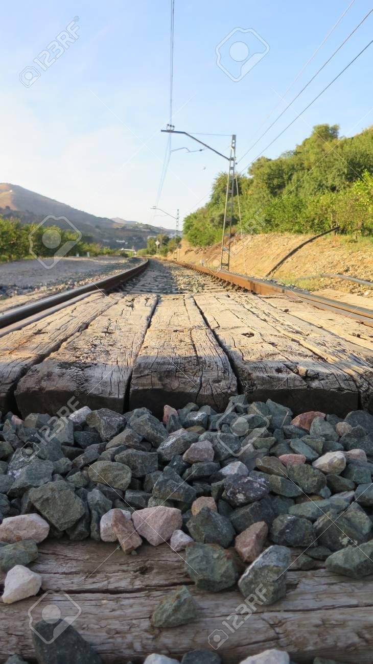 Railway crossing in rural cut with wooden sleepers near Alora,