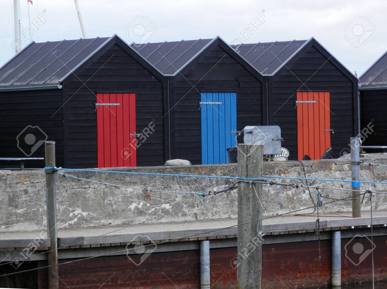 Row Of Black Boat Sheds With Painted Doors In Southern Denmark