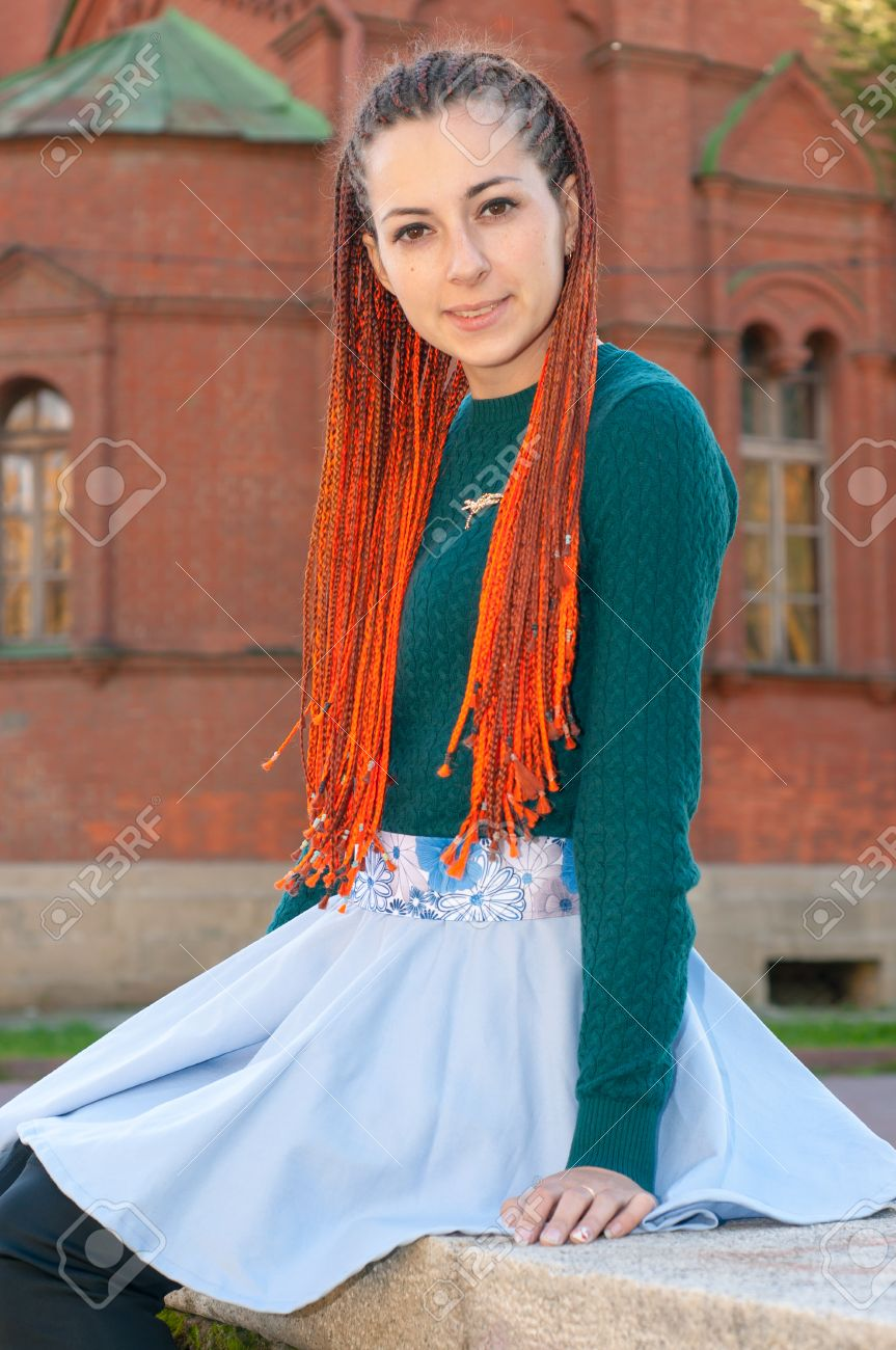 Portriat of young woman with orange braids. Girl with long red..