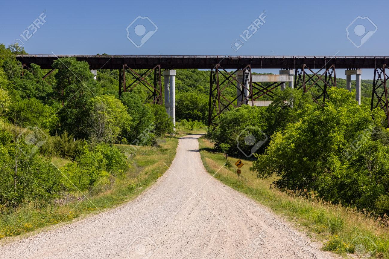A gravel road leading to a high trestle railroad bridge. - 171340073