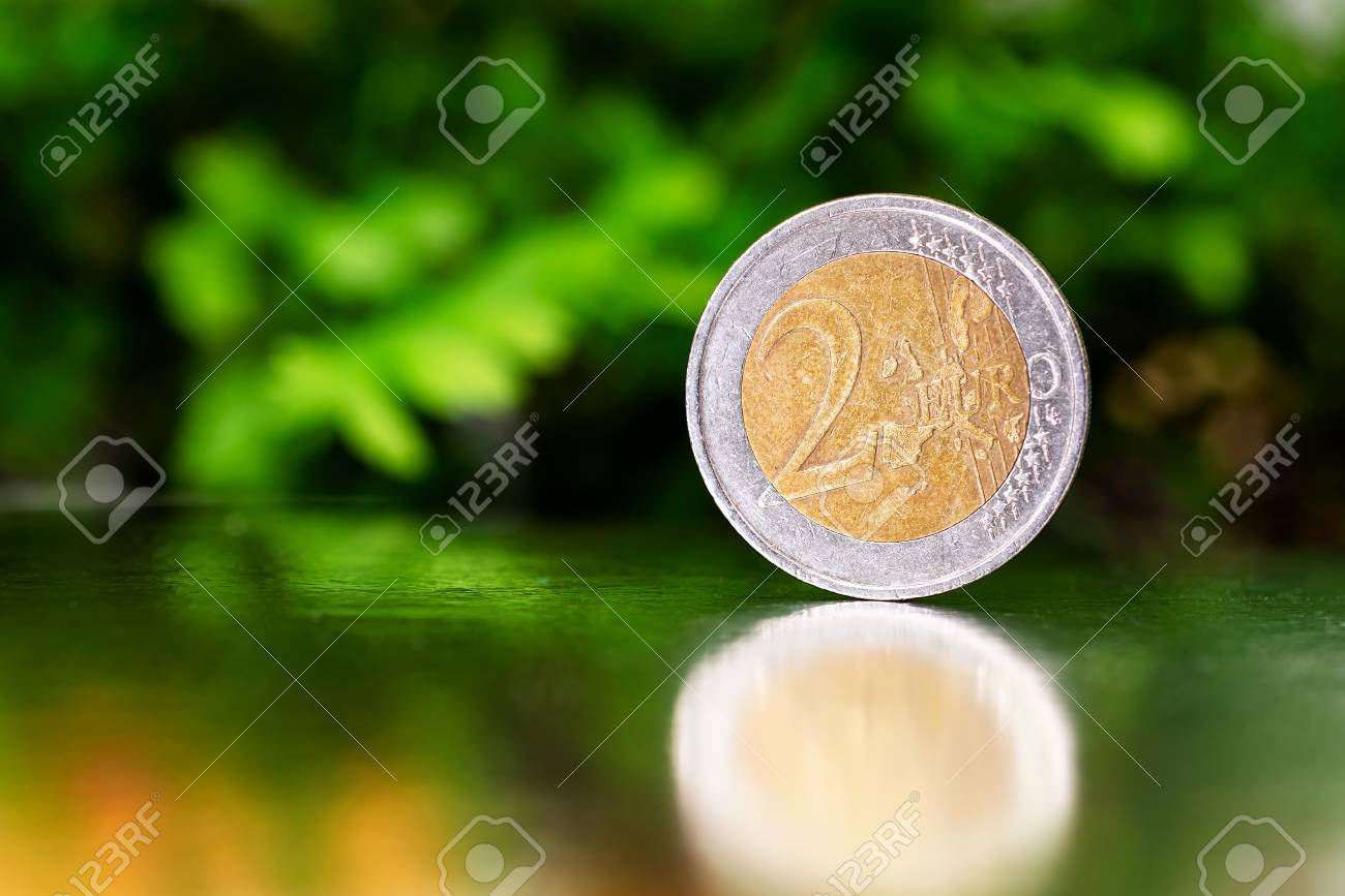 two euro coin closeup on silver and green background. - 104839942
