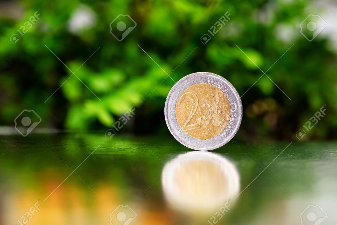 two euro coin closeup on silver and green background. - 106439925