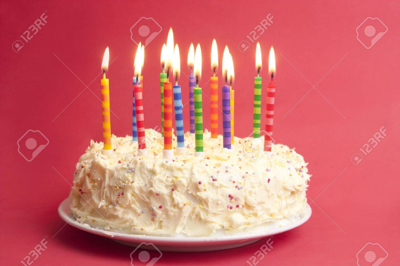 Birthday Cake With Lots Of Candles On A Red Background Stock Photo