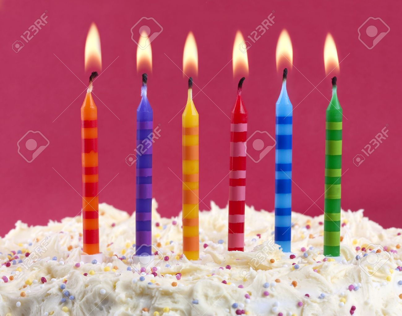 birthday cake with 6 coloured candles on a red background Stock Photo - 8983638