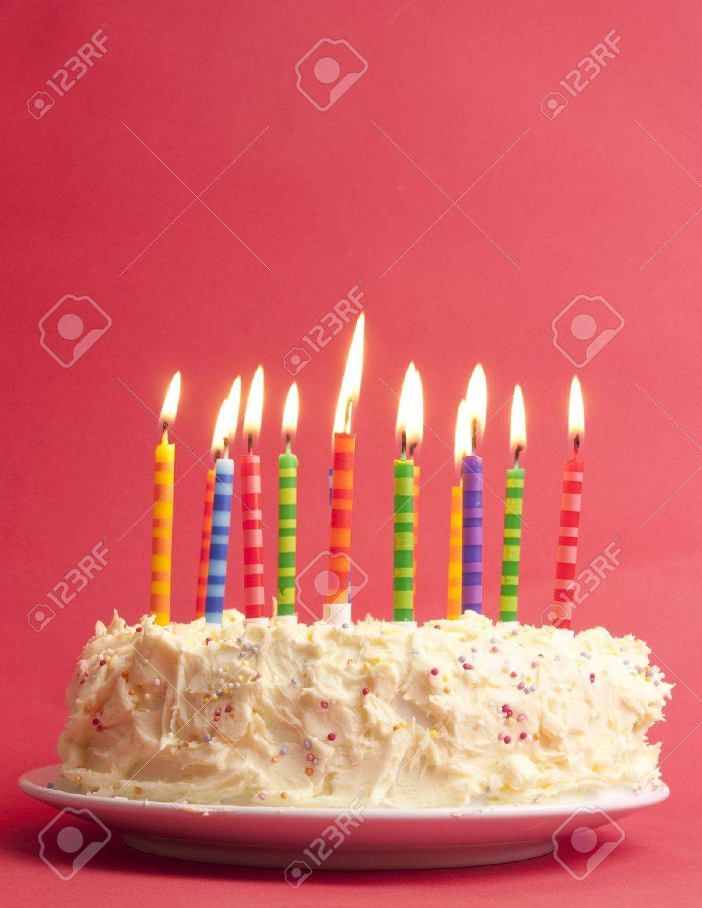 Birthday Cake With Lots Of Cute Striped Candles Shot On A Red