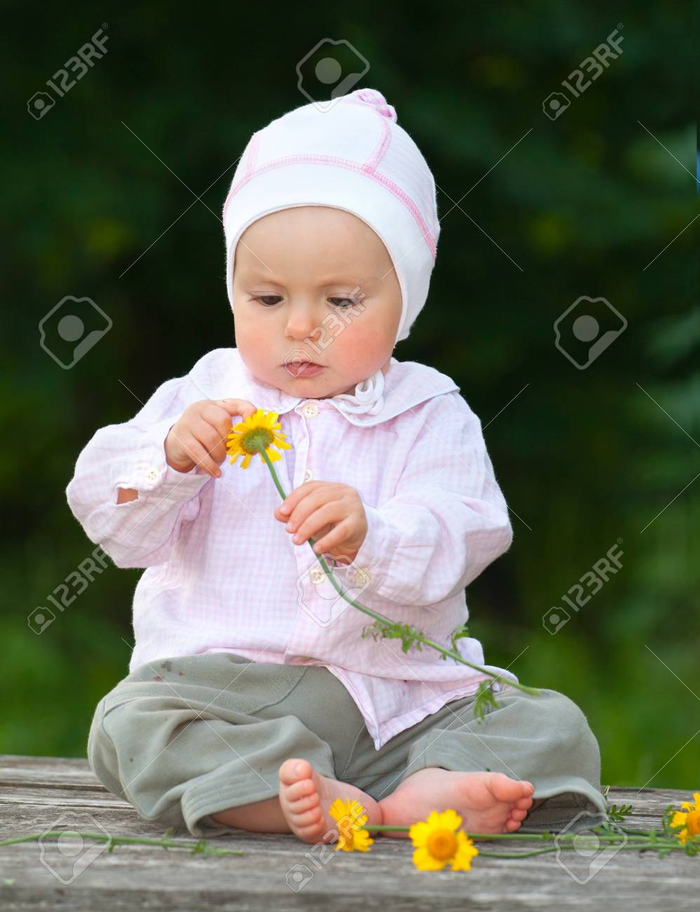 Adorable one-year baby sitting on the table with flowers Stock Photo - 13055910