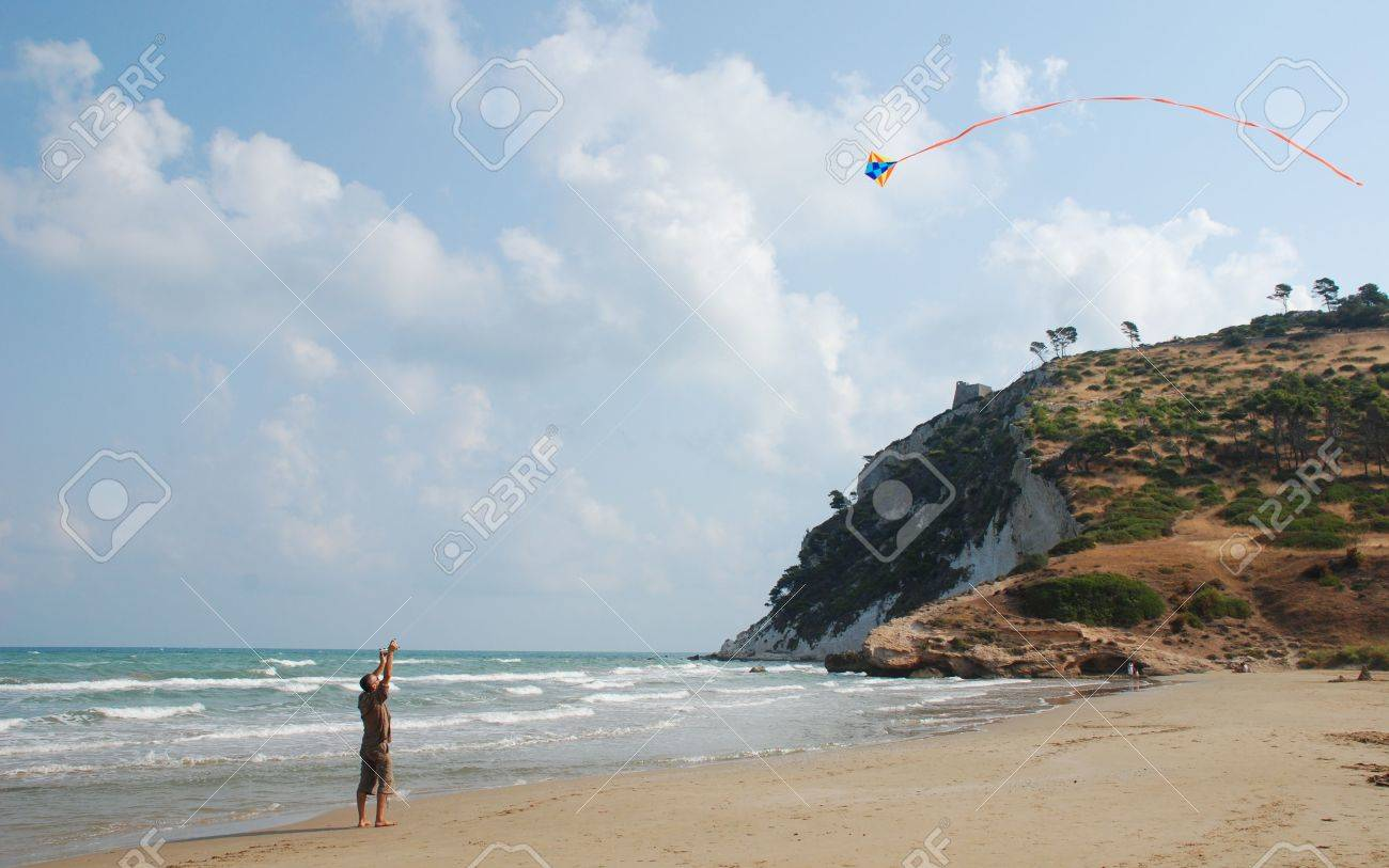 A man stands on a southern Italian beach flying his kite in the strong wind Stock Photo - 3942927