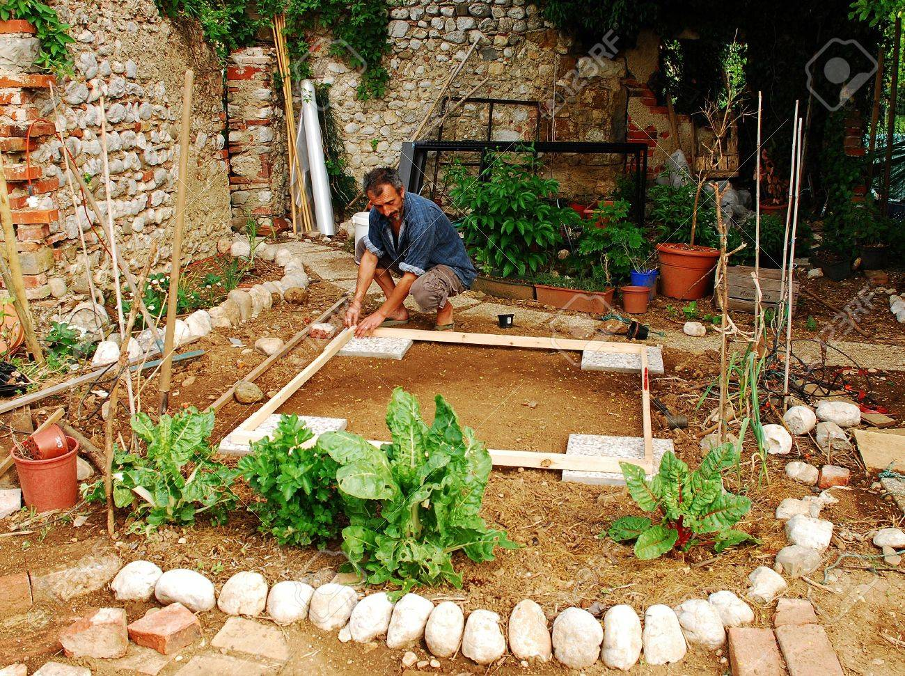 A Man Prepares A Small Patch Of Land Which Has Been Levelled.. Stock ...