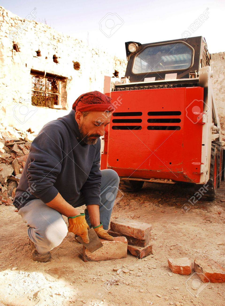 A man scrapes excess cement from antique bricks being salvaged for further architectural use from the demolition site of an old Italian farm building Stock Photo - 8186464