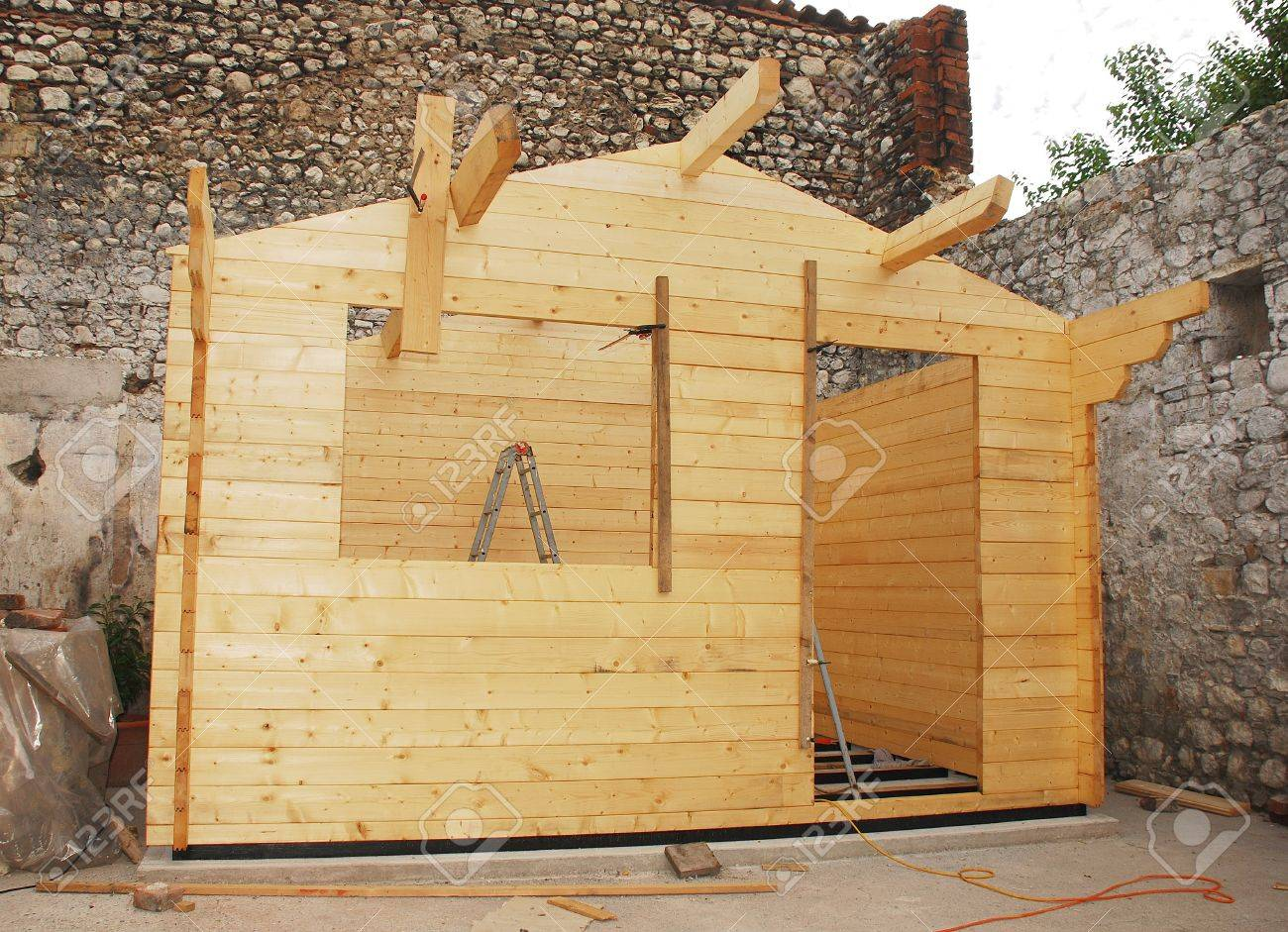 A partially built small prefabricated wooden cabin on a concrete base. The wall beams are in place up to the roof level and the roof rafters have been placed. It is  located within the old stone walls of a now derelict Italian farmhouse Stock Photo - 8475364