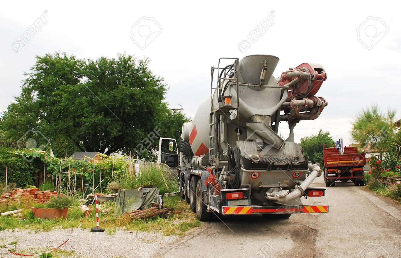 A concrete mixer truck delivering concrete to a small domestic