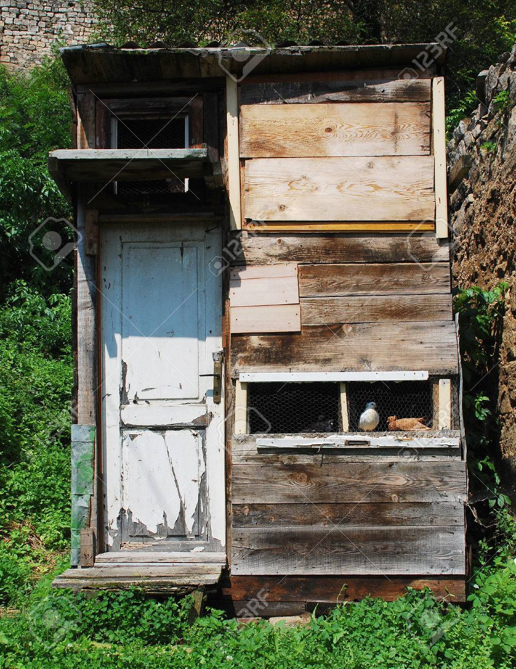 A wooden home-built pigeon coop made from scavenged wood including