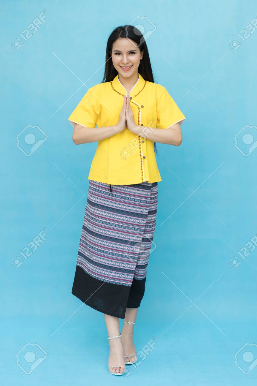 ac68c92dd Portrait of asian young girl in traditional thai dress praying isolated on  blue sky background.