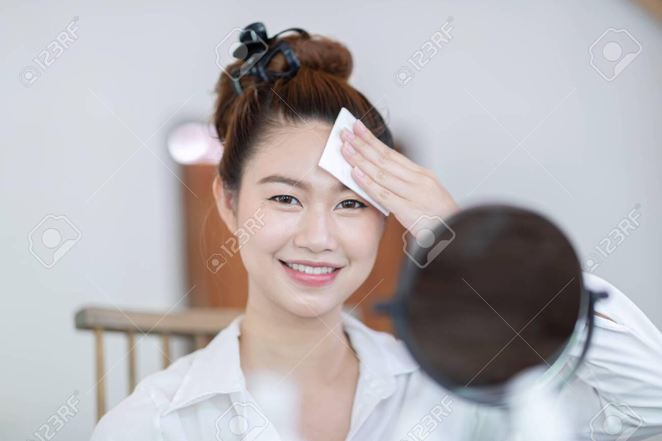 Portrait of a Beauty young woman brunette cosmetics looking in the mirror using tissue with toner for cleaning make up with fresh healthy facial skin,feeling so fresh and happiness,Beauty and Cosmetic - 138577299