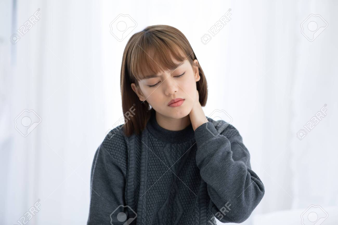 young Asian woman sitting on bed has neck pain after wake up in the morning,Healthcare Concept - 139112321