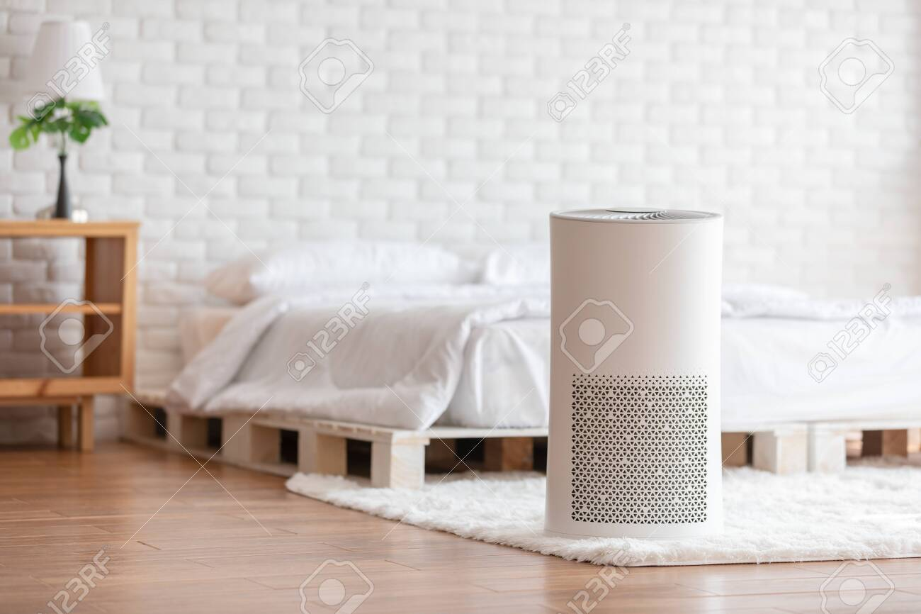 Air purifier in cozy white bed room for filter and cleaning removing dust PM2.5 HEPA in home,for fresh air and healthy life,Air Pollution Concept - 141259835