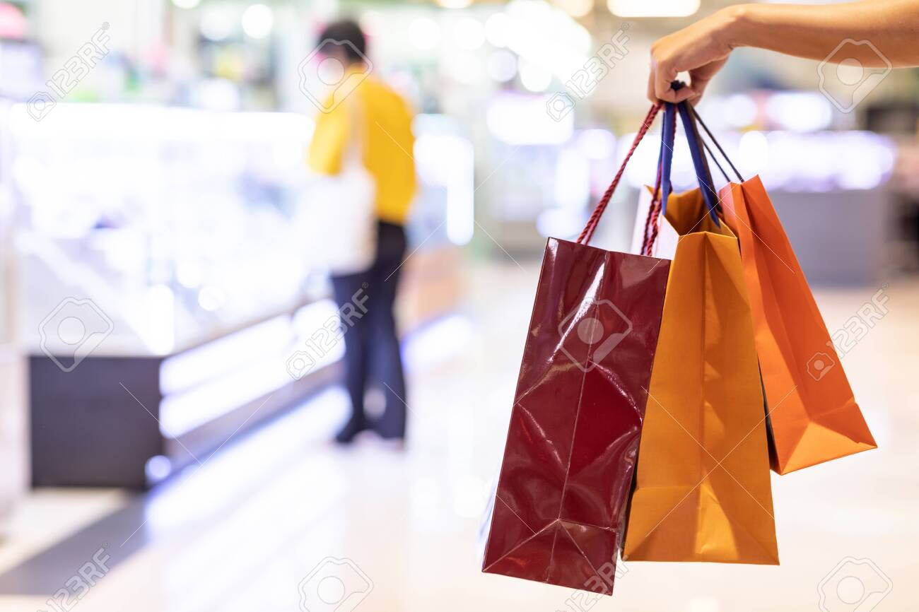 Close up Woman holding shopping bags in her hand walking in shopping mall,Shopping Concept - 144696145