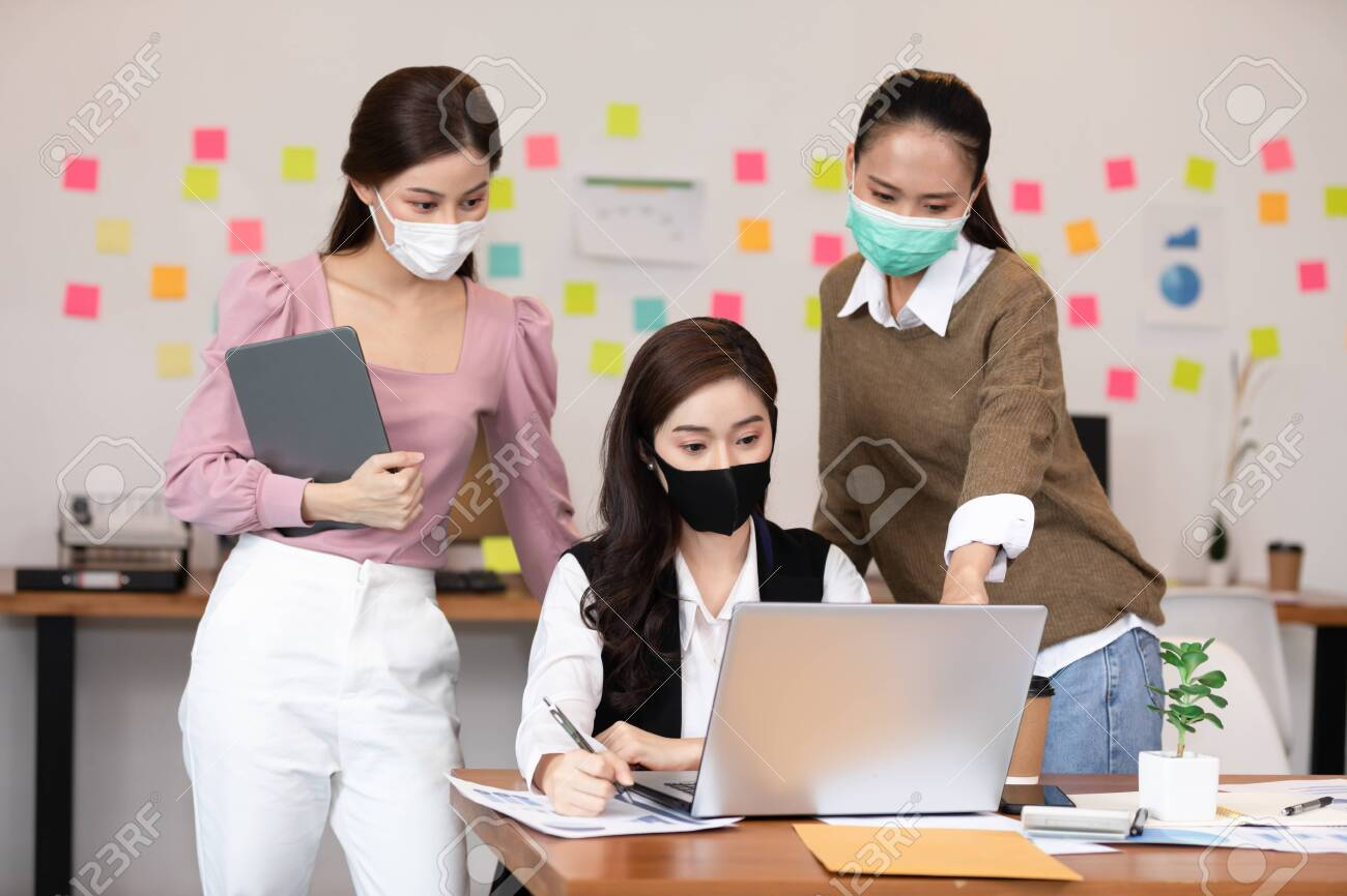 Group of business young woman wearing face mask meeting and working together for discussion and brainstroming to get ideas or marketing solution with social distance due virus pandemic - 156306314