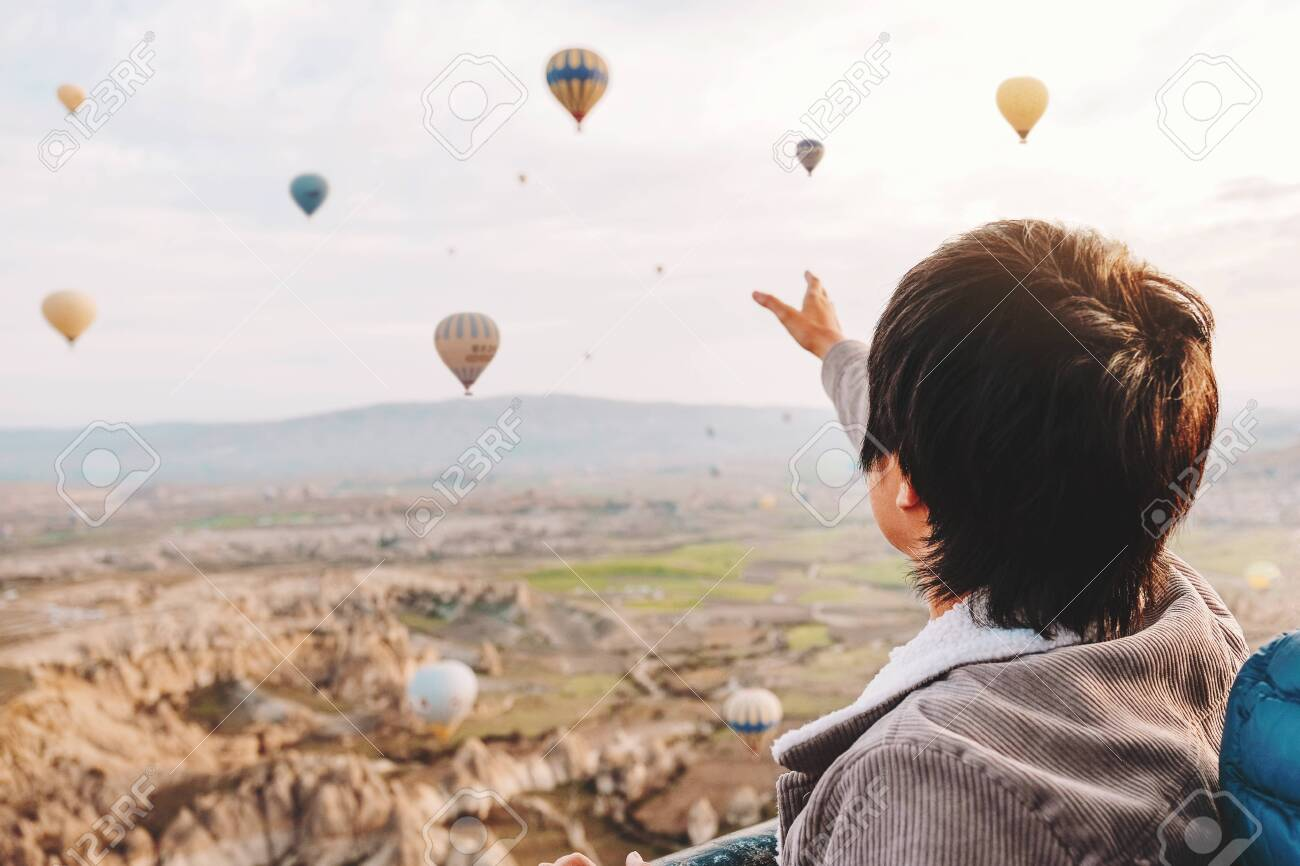 Asian man watching colorful hot air balloons flying over the valley at Cappadocia, Turkey This Romantic time - 137054510