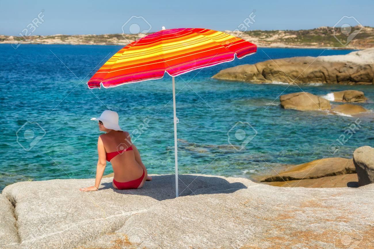 mujer en bikini rojo y sombrero grande disquete blanco sentado bajo una sombrilla de rayas - Sombrillas De Playa Grandes