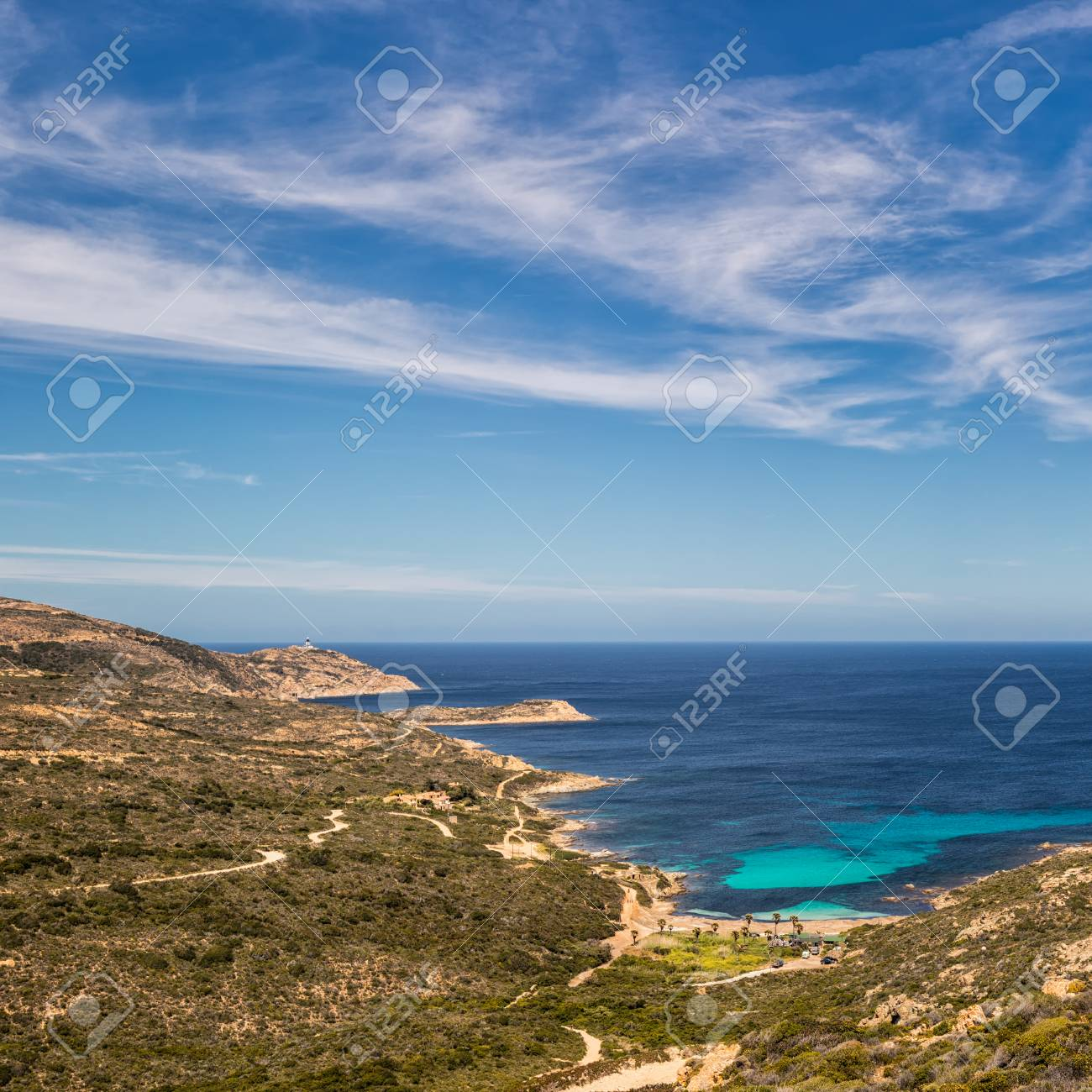 c00969008837 ... near Calvi on the west coast of Corsica looking towards lighthouse in  distance and turquoise Mediterranean sea under deep blue sky with wispy  clouds
