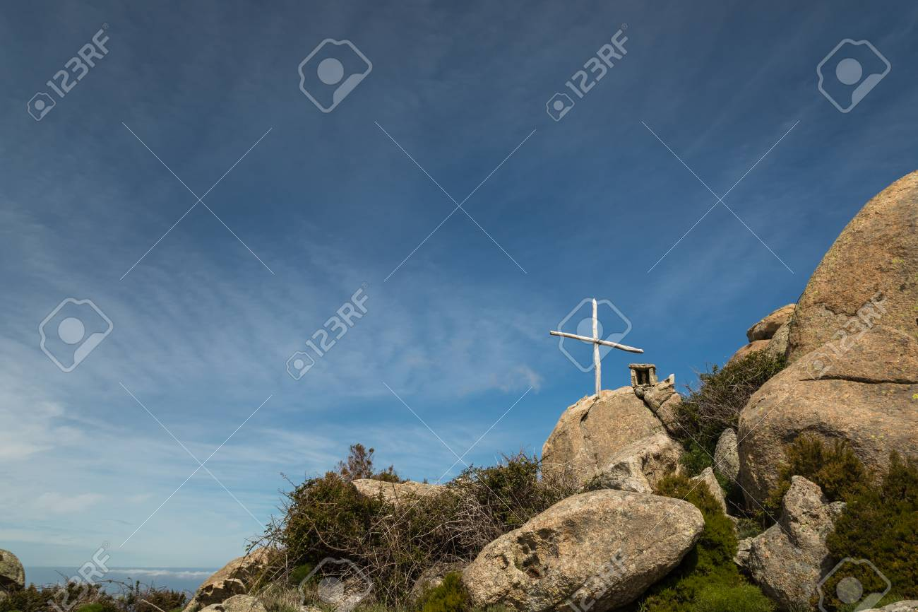 Wooden cross and stone memorial on a rock against a blue sky outside the Refuge de Prunincu on the route to Monte Astu in northen Corsica - 78249192